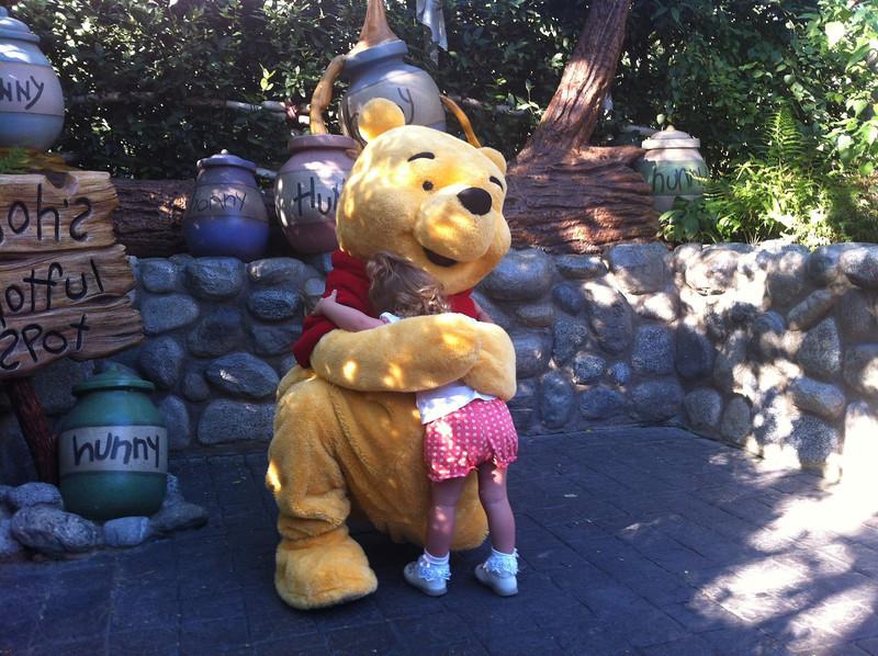 Eva gives Winnie the Pooh a huge hug.