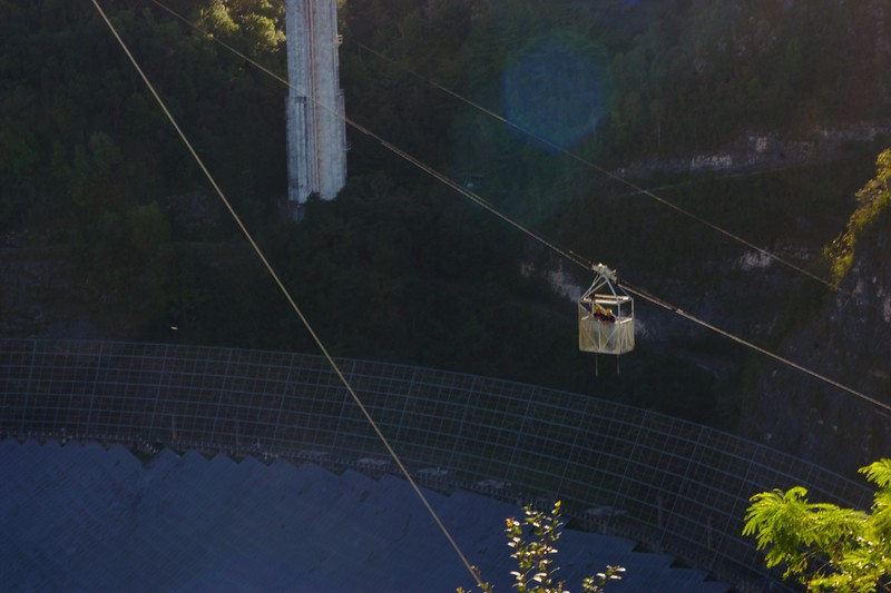 Arecibo dish with workers in tram.