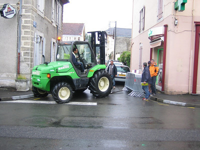 Cute little tractor sets up barriers along the tour course through town.