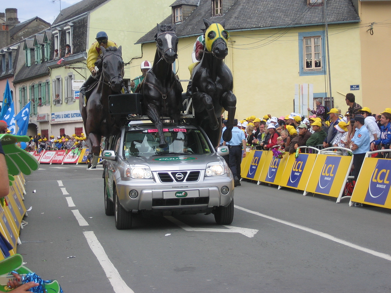 PMU seemed to be some sort of horse racing company ?? They sponsor the green jersey and handed out the big green hands for people to wave during the sprint finish.