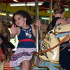 Debby High — For Montgomery Media<br /> Violet Wilkerson, 4, waves to her dad as she passes by while riding the Perkasie Carousel on Memorial Day, May 25.