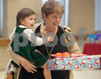 photo by Sarah A. Miller/Tyler Morning Telegraph  Tyler Morning Telegraph employee Shirley Roy picks up a present for her granddaughter Lana Roy, 2, Sunday at the 101 annual T.B. Butler Publishing Christmas party.