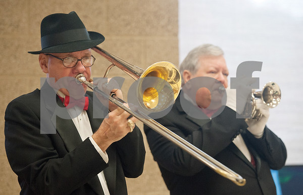 photo by Sarah A. Miller/Tyler Morning Telegraph  Musicians Bobby Overall, left, and Ken Barham, right, perform holiday music Sunday at the 101st annual T.B. Butler Publishing Christmas party.