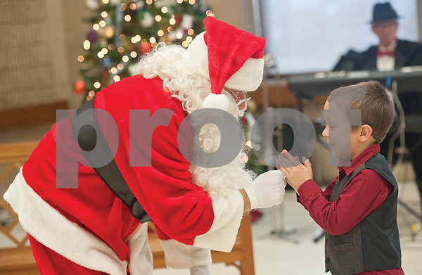 photo by Sarah A. Miller/Tyler Morning Telegraph  Ben Alanis, 6, says goodbye to Santa Claus Sunday at the 101 annual T.B. Butler Publishing Christmas party. Alanis is the nephew of Tyler Morning Telegraph employee Steven Bothwell.