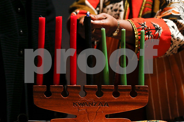 Bobbie Ford Thornton lights a candle during a Kwanzaa celebration at the Tyler Public Library in Tyler, Texas, on Tuesday, Dec. 26, 2017. The African-American Cultural Events Committee will host an event each night of Kwanzaa. (Chelsea Purgahn/Tyler Morning Telegraph)