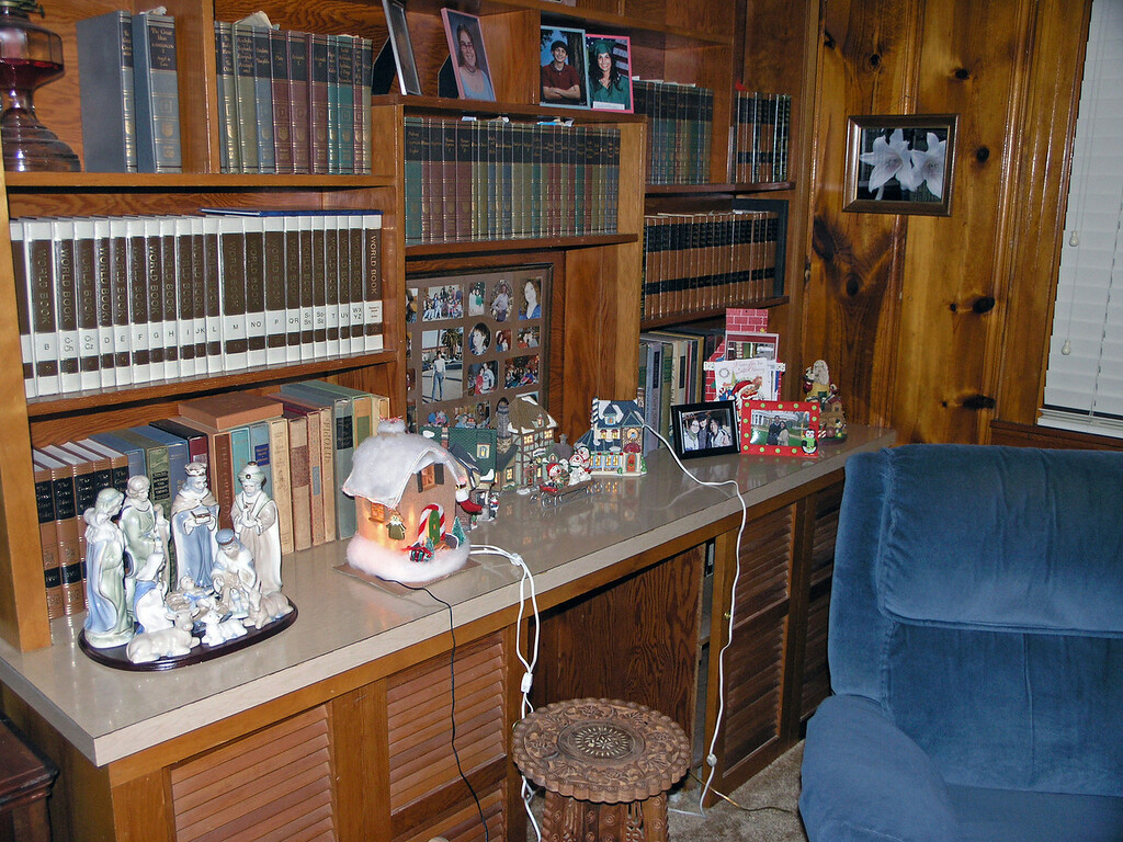 """Dec 17.  It's time to """"Deck the Halls with Bow Wow Charlie.""""  Gmom has begun to arrange her Christmas stuff.  In the right corner, Gmom placed pictures of those family members who will not be able to join us in Jena for Christmas."""