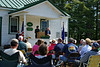 Staff Sargent Esther Kavan speaking during the Memorial Day ceremony at Belgrade, ME, while Master of Ceremonies Robert A. Early and the Reverend William Meyer of Union Church, seated, look on.
