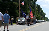 "Ronald ""Kip"" McClure leads a Color Guard of Boy Scouts and Girl Scouts at the start of the Memorial Day ceremony in Belgrade, ME."