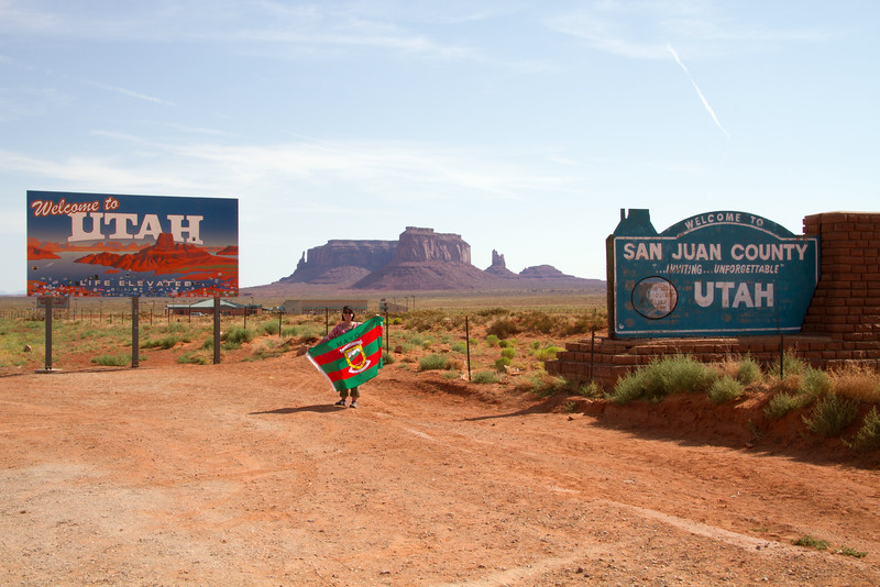 Louise with the Mayo Flag at the state line between Arizona and Utah