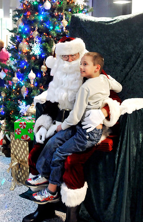 John P. Cleary |  The Herald Bulletin<br /> Jonathan Pierce, 9, gets his picture taken with Santa at Anderson City Building Friday evening before the Christmas Parade kicks off.