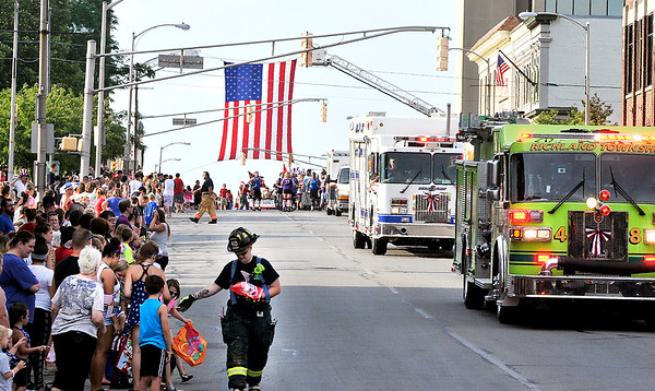 John P. Cleary    The Herald Bulletin<br /> A firefighter passes out candy as area emergency equipment rolls down Main Street in Anderson's Independence Day Parade Monday evening.