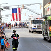 John P. Cleary |  The Herald Bulletin<br /> A firefighter passes out candy as area emergency equipment rolls down Main Street in Anderson's Independence Day Parade Monday evening.
