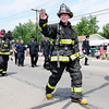 Don Knight | The Herald Bulletin<br /> A Chesterfield-Union Township firefighter waves to the crowd during the Chesterfield Independence Day Parade on Tuesday.