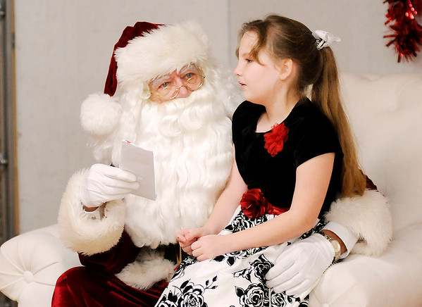 Don Knight | The Herald Bulletin<br /> Megan Donn, 9, delivers her Christmas list to Santa Claus during the <br /> the city of Anderson's Christmas Celebration on Saturday. Santa will be at Dickmann Town Center Park for the next two Saturday's from 1 to 4 p.m.