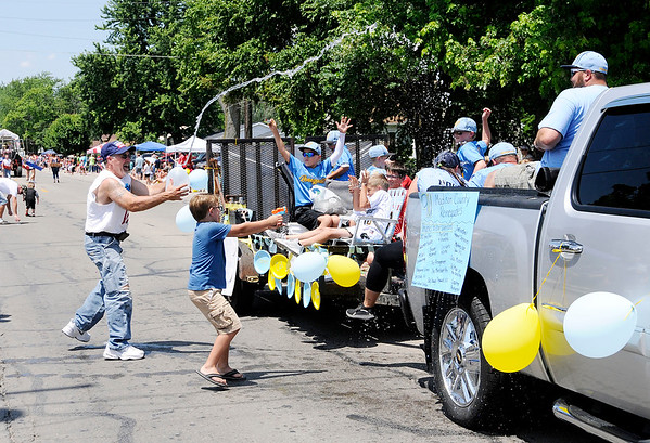 Don Knight | The Herald Bulletin<br /> Travel Team Madison County Renegades get doused but probably didn't mind since it was near 90 degrees during Chesterfield's Independence Day Parade on Thursday.
