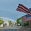 American flags decorating Old City Hall blow in the wind as a rainbow appears over downtown Fitchburg after a rainstorm on Thursday afternoon. SENTINEL & ENTERPRISE / Ashley Green