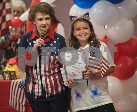 """Jo Anne McMeans of Prestige Estates Assisted Living gives Lucy Roberts, 9, the """"Spirit of the Young American"""" award during a Fourth of July presentation at Stepping Stone School in Tyler on Tuesday July 3, 2018.   (Sarah A. Miller/Tyler Morning Telegraph)"""