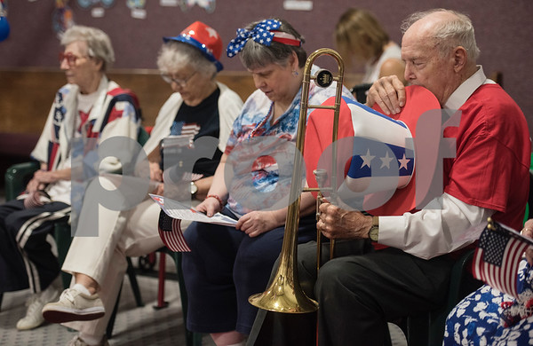 """Korean War veteran Bill Burleson of Tyler takes off his Uncle Sam hat for the invocation after playing the """"Star Spangled Banner"""" on his trombone during a Fourth of July presentation at Stepping Stone School in Tyler on Tuesday July 3, 2018. Residents from Prestige Estates Assisted Living along with women from the Ms. Texas Senior Classic Pageant visited the preschool for a patriotic presentation followed by a student parade at the school.   (Sarah A. Miller/Tyler Morning Telegraph)"""