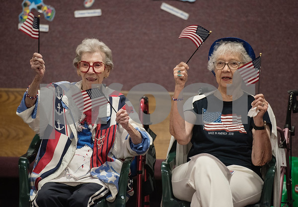 Prestige Estates Assisted Living residents Mary Dowell and Barbara Mosley waive American flags during a Fourth of July presentation at Stepping Stone School in Tyler on Tuesday July 3, 2018. Residents from Prestige along with women from the Ms. Texas Senior Classic Pageant visited the preschool for a patriotic presentation followed by a student parade at the school.   (Sarah A. Miller/Tyler Morning Telegraph)