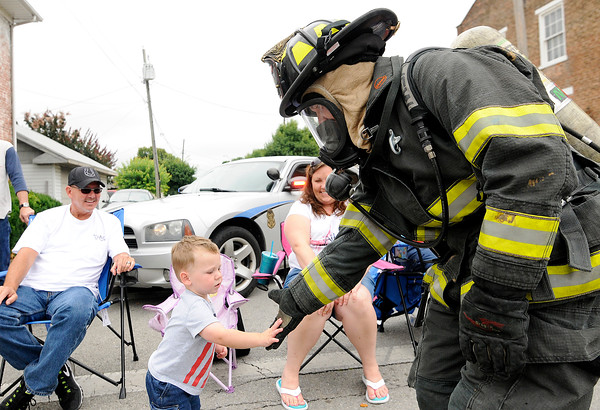 Don Knight | The Herald Bulletin<br /> A member of Richland Township's fire department greets a young boy in the crowd during the Chesterfield 4th of July Parade on Monday.