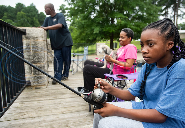 Eric Moaning, Schwanda Moaning and Eriunna Moaning, 11, fish at the pond outside of the Glass Recreation Center in Tyler on July 4, 2019.  (Sarah A. Miller/Tyler Morning Telegraph)
