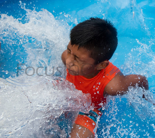 Giovahni Bentiaz, 7, splashes down into water from an inflatable bounce house pool slide at his home in Tyler on July 4, 2019.  (Sarah A. Miller/Tyler Morning Telegraph)