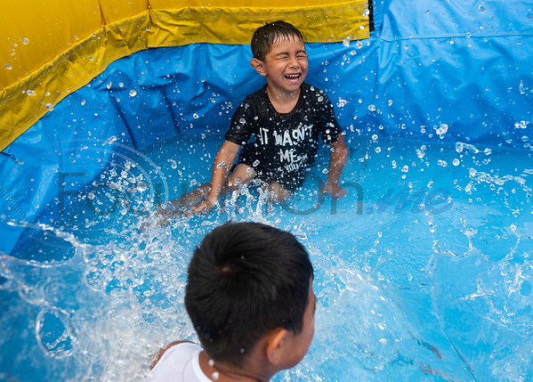 Siblings Carlo Marquez, 5, Ben Marquez, 6, splash down into water from an inflatable bounce house pool slide with at their home in Tyler on July 4, 2019.  (Sarah A. Miller/Tyler Morning Telegraph)