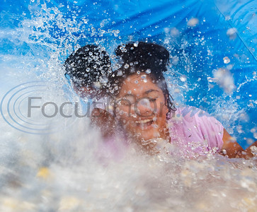 Maya Marquez, 13, splashes down an inflatable bounce house pool slide with her sibling at their home in Tyler on July 4, 2019.  (Sarah A. Miller/Tyler Morning Telegraph)