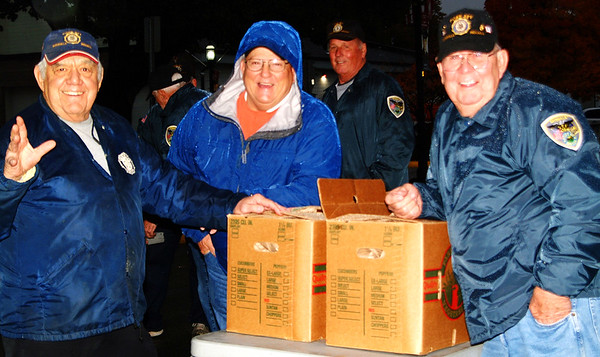 Debbie Blank | The Herald-Tribune Prell-Bland American Legion Post 271 members (from left) Mike Gutzwiller and Richard Narwold, Batesville, and Johnny Baumer, Oldenburg, prepare to pass out goody bags in front of the Memorial Building at the end of the 2018 Batesville Halloween Parade.