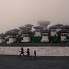 Kids run past the Chortens (stupas) at Dochula pass.