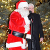 "Debbie Blank | The Herald-Tribune<br /> Santa leads tree lighting participants in singing ""Rudolph the Red-Nosed Reindeer"" as Mayor Mike Bettice watches."