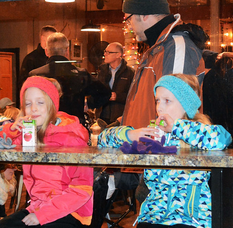 Debbie Blank | The Herald-Tribune<br /> Twins Cecily and Sophia Anderson, 8, Bright, sipped on juice at Amack's Well while watching tree lighting activities from window seats.