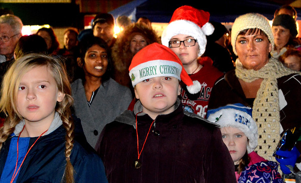 Debbie Blank | The Herald-Tribune<br /> Uriana Arthur (front), 10, Sunman, and Savannah Clark, 14, Batesville, wearing Santa hats, were among hundreds anticipating Santa Claus' arrival downtown in the bike park area south of East Pearl Street between Main Street and Park Avenue.
