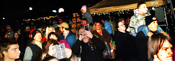 Debbie Blank | The Herald-Tribune<br /> Many kids were on dads' shoulders, the better to view the tree lighting ceremony.