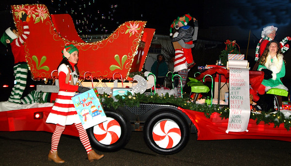 Debbie Blank | The Herald-Tribune<br /> A beautiful sleigh, festive stripes and Santa's list of children were all part of this float.