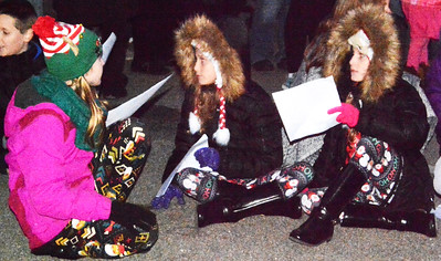 Lookalike girls in matching coats listened to children sing before the procession began.