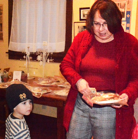 Before the parade, Terry Messerschmidt, Batesville, and granson Theo Wissel, 4, Zionsville, purchase a plate of cookies at the Batesville Area Historical Society fundraiser at the Batesville Historical Center.