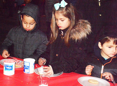Felipe Retzner (from left), 6, Batesville, and Mia Alexander, 7, and brother Sam, 4, Moores Hill decorate cookies.