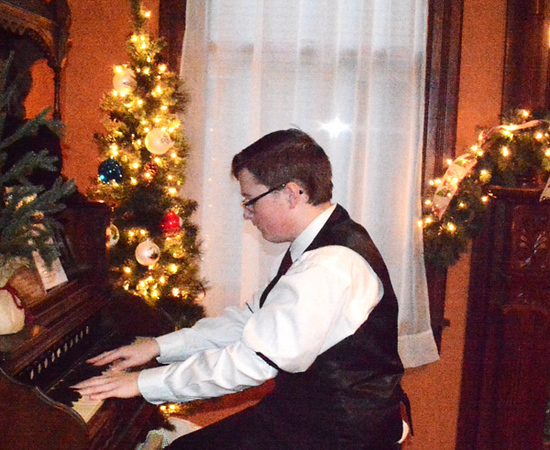 Zach Womack, 17, Brookville, played holiday tunes on the the pump organ at the Batesville Historical Center for visitors who were purchasing Christmas cookies and exploring the trains display before the parade and tree lighting got underway.