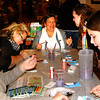 Debbie Blank | The Herald-Tribune<br /> Angie Johnson (from left), Jessica Imel, Susie Stirn, Tri-State Artisans co-owner Sara Mustaine and Jocelyn Waterhouse make snowman ornaments at the booth sponsored by the business.