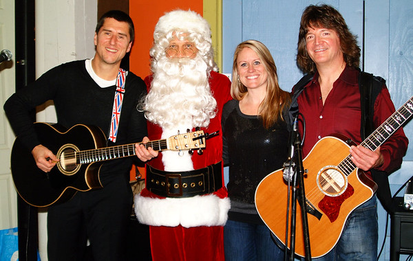 Debbie Blank | The Herald-Tribune<br /> Santa boogied to the music performed by (from left) Mitch Tidman, Shannon Kramer and Frank Zielinski.