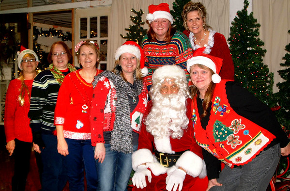 Debbie Blank | The Herald-Tribune<br /> Santa poses with Ugly Sweater Contest participants: (top row from left) first place winner Ashley Schuck and Miss Congeniality Ginger Flannery; (bottom row from right) third place winners Annette Morrison and Katrina Lock with other participants Pam Huster, Terry Messerschmidt and Joan Schornick, wearing a blonde wig.