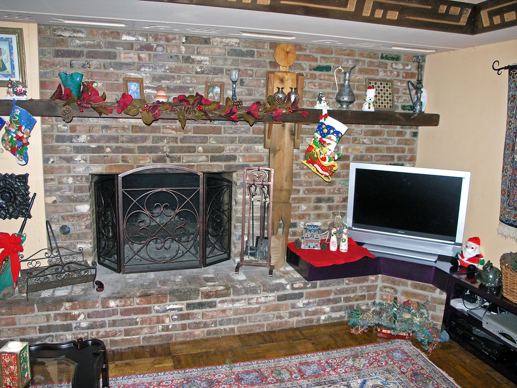 Dec 18.  The fireplace mantle is decorated.  A little Santa Claus sits on the shelf Asghar built for the TV and recording equipment.