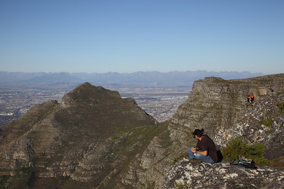 People sitting on the edge of Table Mountain looking down on Cape Town.  Cape Flats in the background beyond Devil's Peak.