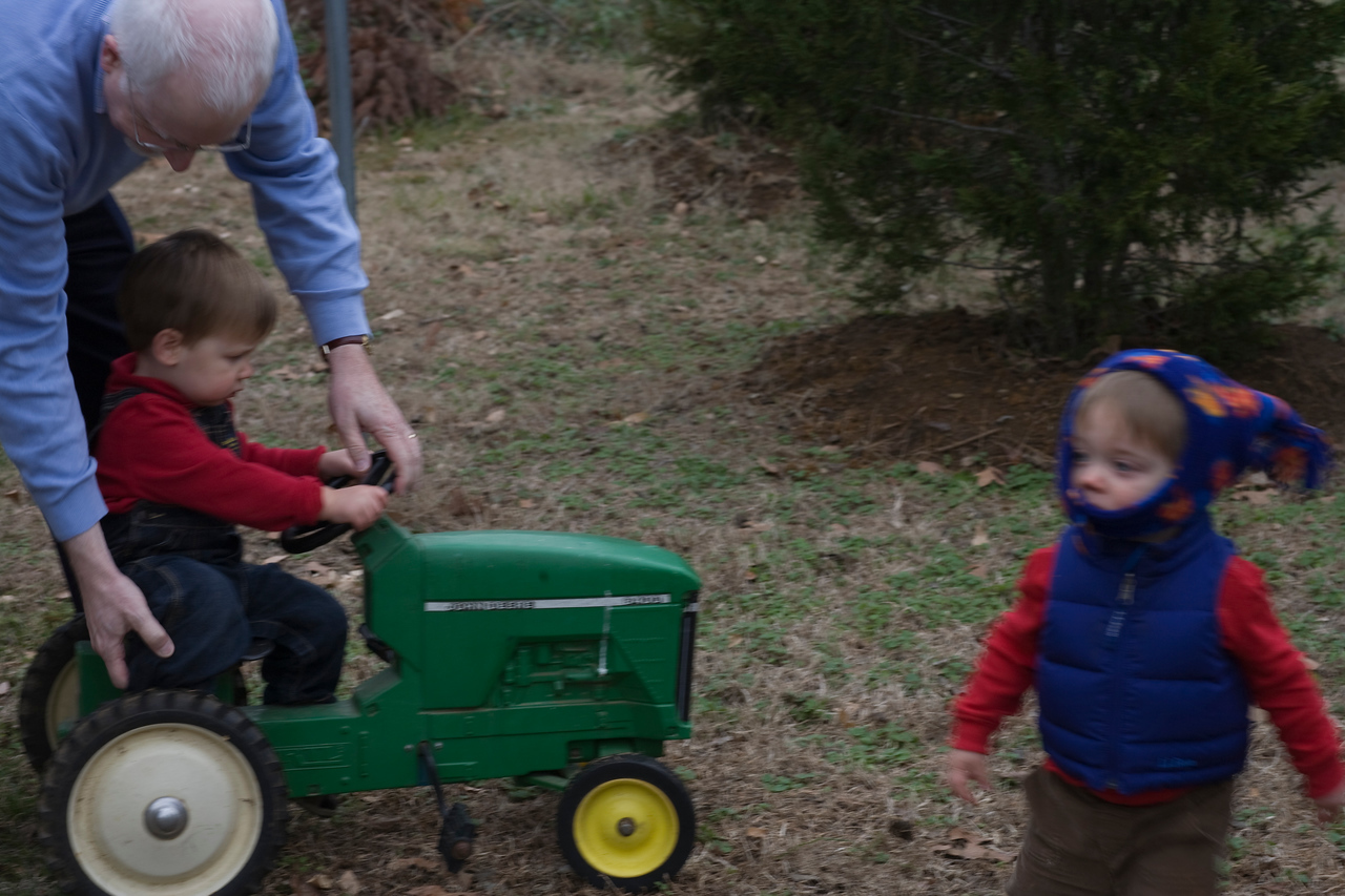 Scott pushes the tractor as Caleb rides around