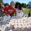 50th anniversary of Chelmsford's 4th of July celebration and parade. Volunteers Gregory Chagnon of Hudson, N.H, and his girlfriend Teresa Dao prepare water cups for the runners near Wiggin Street. (SUN/Julia Malakie)
