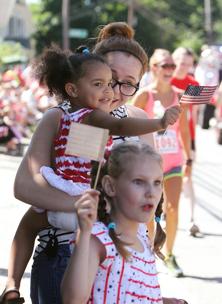 50th anniversary of Chelmsford's 4th of July celebration and parade. Desti Eszaberny Justason of Clinton holding her sister Adelynne Geer, 3, watch parade with their cousin Olivia Moody, 7, of Nashua. (SUN/Julia Malakie)