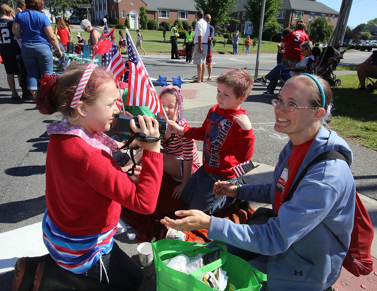50th anniversary of Chelmsford's 4th of July celebration and parade. From left, Colleen McCarthy, 11, shooting video, her sister Erin, 9, brother Sean, 7, and mother Katie McCarthy of Chelmsford, wait for race and parade. (SUN/Julia Malakie)