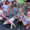 Chelmsford 4th of July parade. Harper Magliozzi, 4, second from right, and her sister Brooklyn, 2, right, stay cool in the shade before the parade with their 12-week old champagne Lab puppy, Skye, who was cooling off in a puddle of water and attracting admirers. (SUN/Julia Malakie)