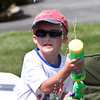 William Turner, 5, of Chelmsford, sprays passersby while waiting for the Chelmsford 4th of July parade.  (SUN/Julia Malakie)